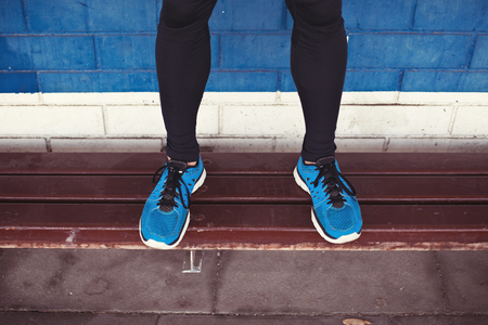 close-up of athletes legs with running shoes standing on bench