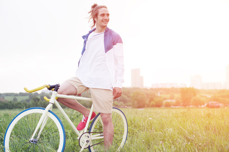 young long hair man in blank t-shirt sitting on his bicycle in the field (intentional sun glare and vintage colors)