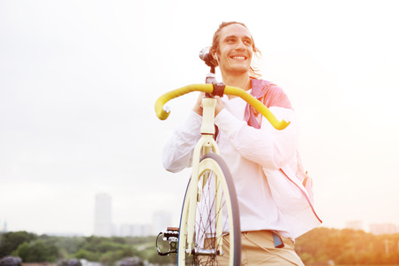 intentional: smiling man holding bicycle in green field (intentional sun glare and bright color)