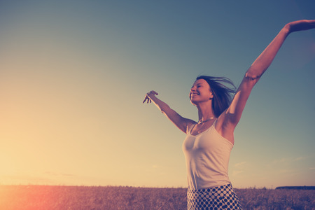 intentional: Girl in dress enjoying sunset in the field outdoors (intentional sun glare and vintage color) Stock Photo