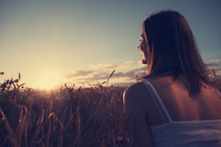 Young handsome girl watching beautiful sunset outdoors Standard-Bild