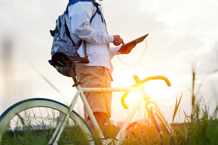 young man with bicycle in the green field touching tablet computer (intentional sun glare and dark colors, focus on tablet)