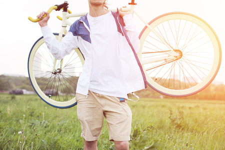 intentional: young man in blank t-shirt holding bicycle in green field (intentional sun glare and bright colors)
