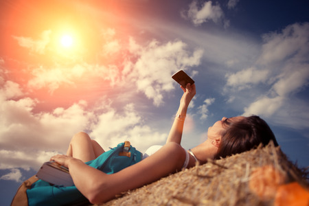 Girl lying on haystack with backpack and mobile phone (intentional sun glare and lens flares, lens focus on phone)