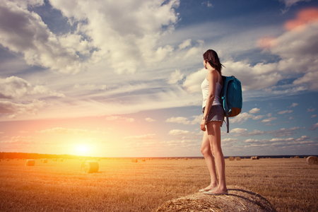 Young and handsome traveler girl with backpack standing on haystack looking at sunset (intentional sun glare)