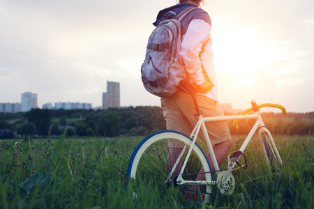 young man with bicycle in the green field looking at sunset (intentional sun glare and dark colors) Stock Photo