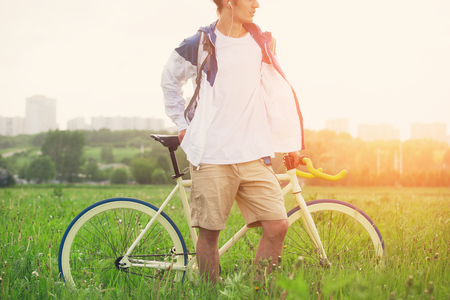 intentional: Man in blank t-shirt with bicycle standing in green field (intentional sun glare and bright color)