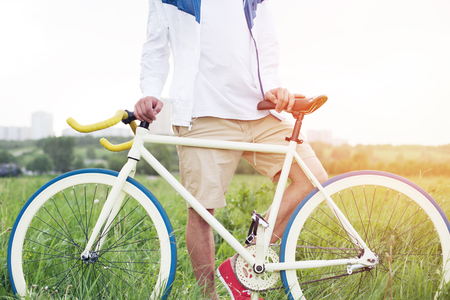 young man standing with bicycle in green field outdoors