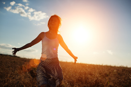 intentional: Happy young girl running in the field at sunset (intentional sun glare and lens flares) Stock Photo