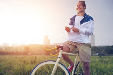 young smiling long hair man with bicycle in green field with smartphone (intentional sun glare and vintage colors, focus on phone)