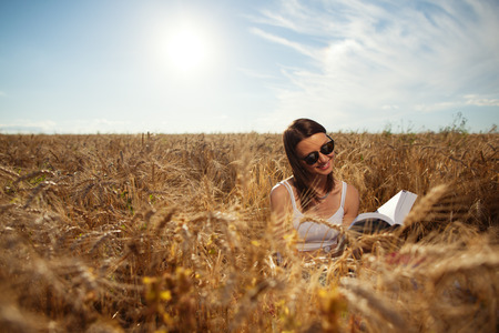 Young and handsome girl reading book outdoors in the field