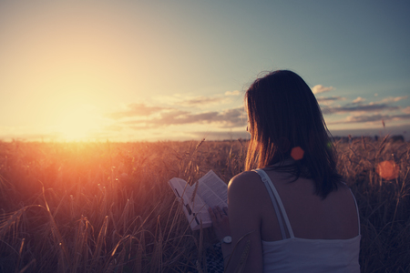 Young handsome girl reading book outdoors in sunset in the field Standard-Bild