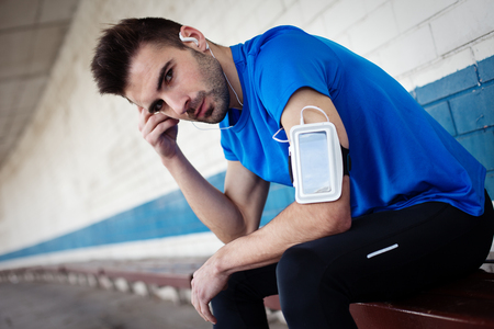 portrait of athlete listening music with smartphone and armband