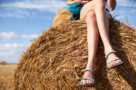 Young and handsome girl sitting on haystack with a backpack