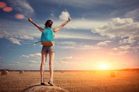 intentional: Happy and young girl with outspread hands and backpack greeting sunset outdoors (intentional sun glare and lens flares)