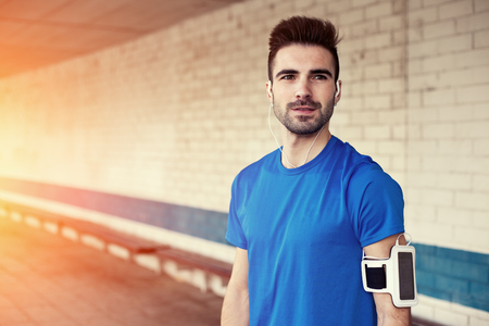 intentional: portrait of handsome athlete with stubble, earphones and armband (intentional sun glare) Stock Photo