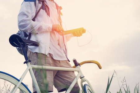 young man with bicycle in the green field with tablet computer at sunset (intentional sun glare and vintage colors, focus on tablet)
