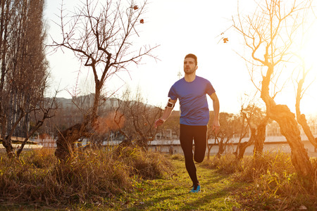 intentional: Handsome young athlete jogging in the park at sunset (little motion blur, intentional sun glare)
