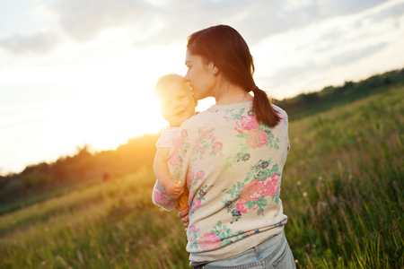 intentional: Happy mother kissing her baby in the park outdoors (intentional sun glare)