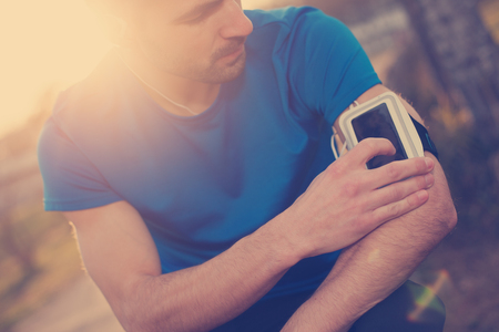 intentional: Athlete touching mobile phone on his arm (intentional sun glare and vintage color)