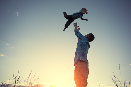 intentional: silhouette of father catching his son in the park at sunset (intentional sun glare and vintage color) Stock Photo