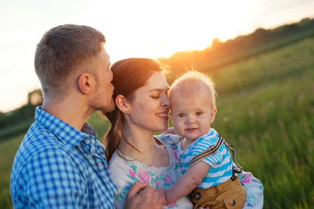intentional: happy young family with baby spending time outdoors (intentional sun glare, lens focus on mother)
