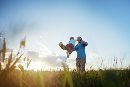 intentional: father playing with his son in the park outdoor (intentional sun glare)