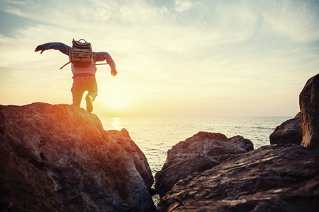 traveler with backpack near sea running to horizon at sunset