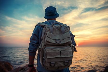 traveler with backpack near sea looking far away at horizon at sunset
