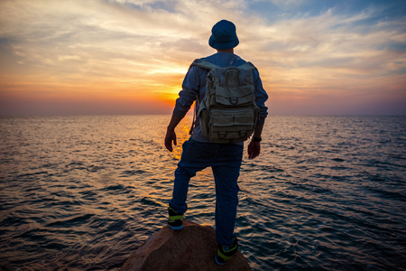 traveler with backpack near the sea looking far away at the horizon at sunset