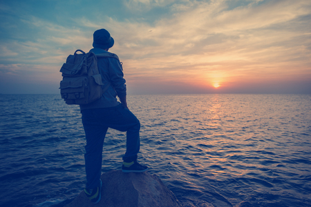 intentional: traveler with backpack near sea looking far away at horizon at sunset (intentional vintage color) Stock Photo