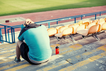 tired athlete after failing resting with a bottle of water sitting on the stairs at stadium
