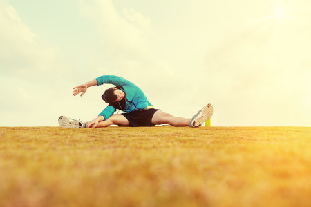 Sportsman doing warming and stretching exercise in the park and yellow grass with sun flare Stok Fotoğraf