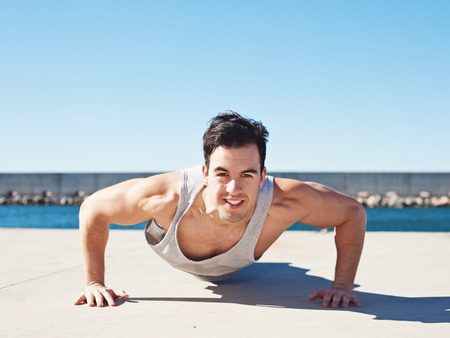 Handsome smiling athlete doing push up outdoors Stok Fotoğraf