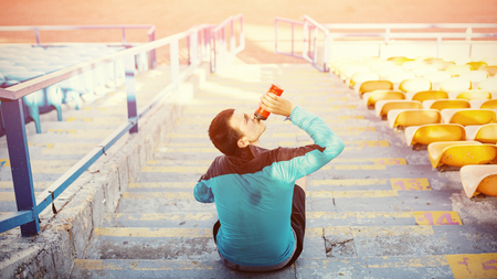 sweaty sportsman drinking water sitting on the stairs Stock Photo