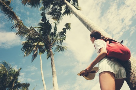 Young and happy girl standing near palm tree at resort on holidays intentional vintage color Standard-Bild