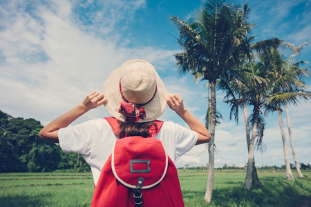 Young girl with straw hat and backpack enjoying her trip in nature at good sunny day