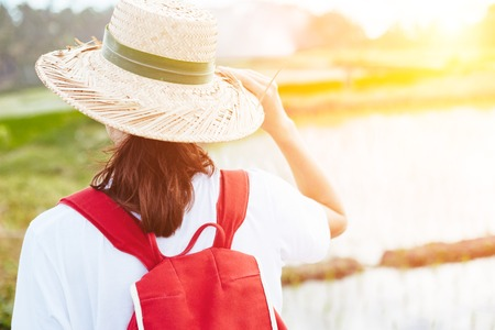 Young girl holding her straw hat and nature walks intentional sun glare Standard-Bild