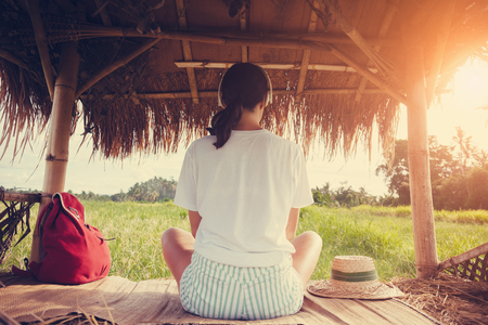 Young girl listening music with headphones in nature under straw roof intentional sun glare and vintage color