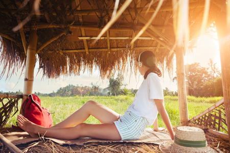 Young girl sitting and listening music with headphones in nature under straw roof intentional sun glare Standard-Bild