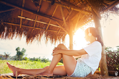Young girl resting and listening music with headphones in nature under straw roof intentional sun glare