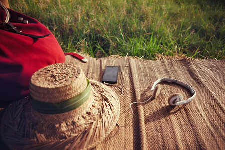 Mobile phone, headphones, hat and backpack in nature