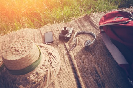 Mobile phone, vintage photo camera, headphones, hat and backpack in nature intentional sun glare