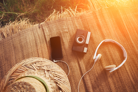 Mobile phone, vintage photo camera, headphones and hat in nature intentional sun glare Standard-Bild