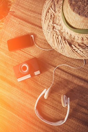 Mobile phone, vintage photo camera, headphones and hat lying on straw intentional sun glare Standard-Bild
