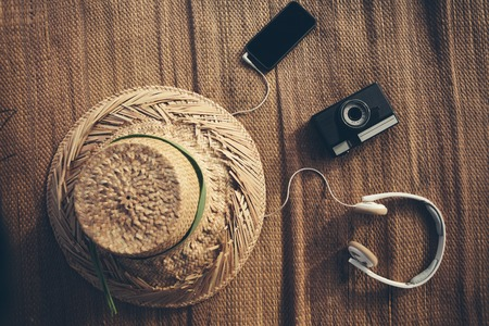 Mobile phone, film photo camera, headphones and hat lying on straw Standard-Bild