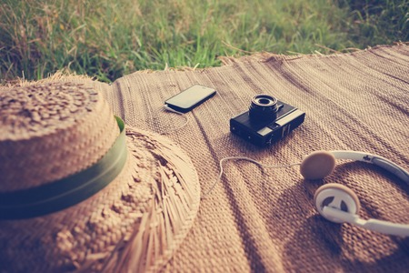 Mobile phone, film photo camera, headphones and hat outdoors