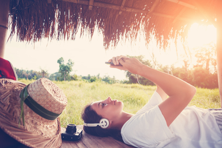 Young happy girl resting outdoors with mobile phone in hands and listening music intentional sun glare and vintage color