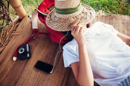 Young girl with straw hat resting outdoors and listening music with headphones at good sunny day Standard-Bild
