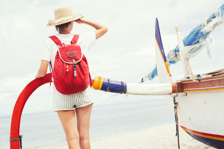Young beautiful woman with backpack and hat standing near sailboat on beautiful island and looking far away